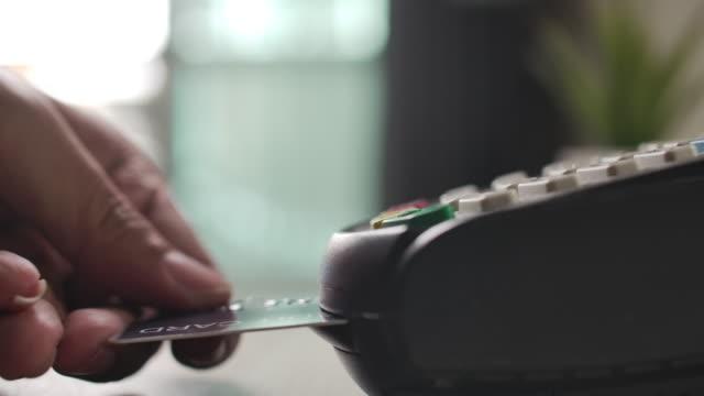 vídeos de stock e filmes b-roll de slow motion using credit card reader inserting credit card in credit card reader - primeiríssimo plano