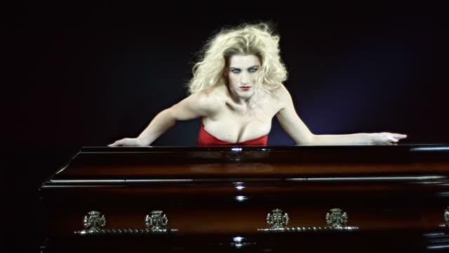 stockvideo's en b-roll-footage met hd slow motion: vampire sensual moving behind a coffin - doodskist