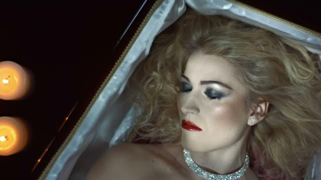 stockvideo's en b-roll-footage met hd slow motion: vampire waking up in a coffin - doodskist