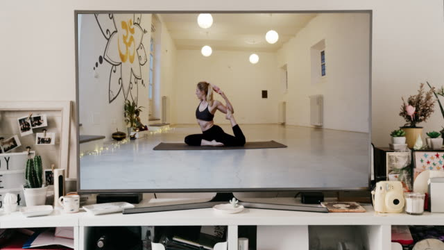slow motion video of a big tv screen with an online yoga video lesson - lotus position stock videos & royalty-free footage