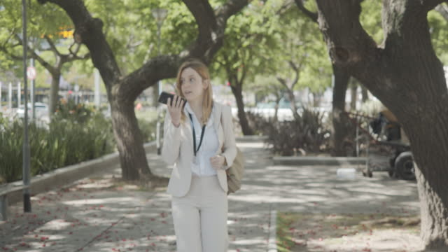 slow motion video of a businesswoman in the city talking on speaker with smartphone - avenida 9 de julio stock videos & royalty-free footage