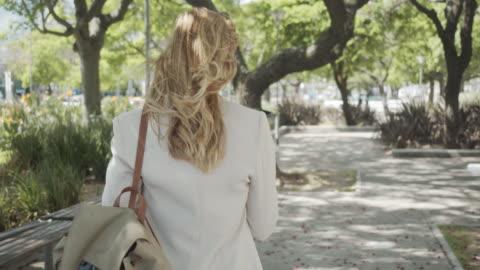 zeitlupenvideo einer geschäftsfrau in der stadt, die mit dem smartphone über lautsprecher spricht - rückansicht - blondes haar stock-videos und b-roll-filmmaterial