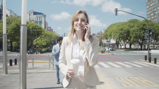 slow motion video of a businesswoman in the city with coffee and smartphone - avenida 9 de julio stock videos & royalty-free footage