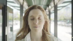 Slow motion video of a businesswoman opening her eyes and looking at camera