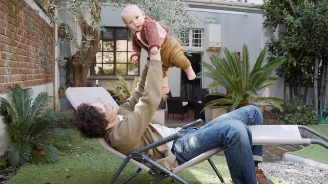 video al rallentatore di un padre che gioca con il suo bambino nel cortile di casa - affettuoso video stock e b–roll