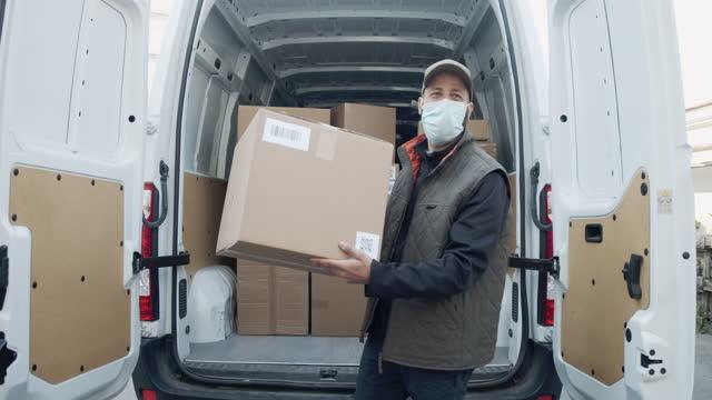 vídeos de stock, filmes e b-roll de vídeo em câmera lenta de um entregador descarregando sua van, segurando um pacote - etnia caucasiana