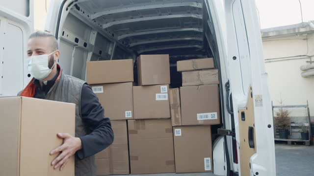 slow motion video of a delivery man unloading his van, holding a parcel - van stock videos & royalty-free footage