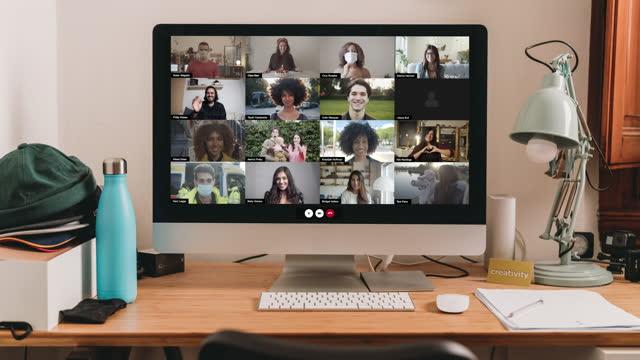 stockvideo's en b-roll-footage met slow motion-video van een desktop-pc met een videoconferentiegesprek op het scherm - grote groep mensen