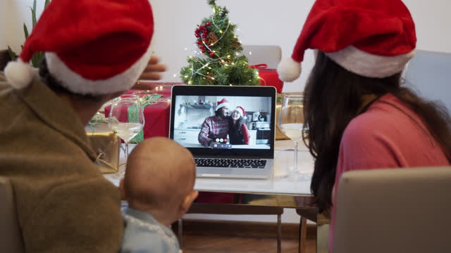 Slow motion video of a family celebrating Christmas with their relatives during a video call