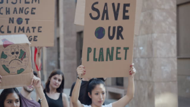 vídeos de stock e filmes b-roll de slow motion video of a group of people participating in a protest against global warming - política