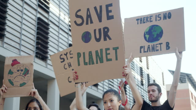 slow motion video of a group of people participating in a protest against global warming - protest stock videos & royalty-free footage