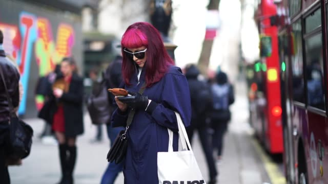 Slow motion video of a guest wearing sunglasses a blue long coat a PAUSE white bag Vetements black shoes with orange heels pink hair and using a...