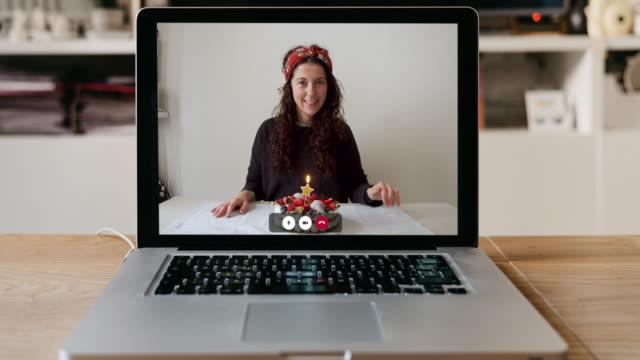 Vidéo au ralenti d'un ordinateur portable avec une femme et son gâteau d'anniversaire sur l'écran