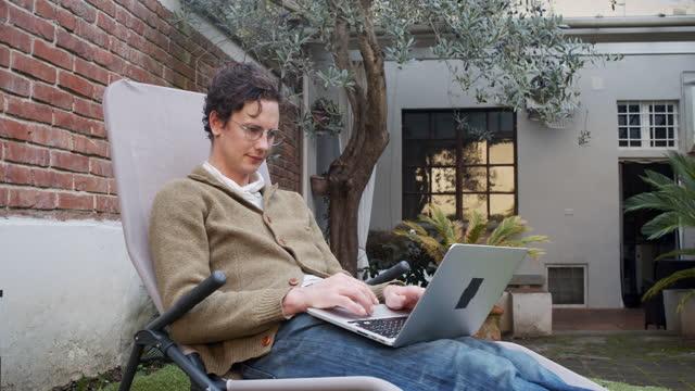 彼はホテルで彼のラップトップで作業している間、男のスローモーションビデオ - リゾート地点の映像素材/bロール