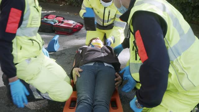 vídeos y material grabado en eventos de stock de video a cámara lenta de una mujer madura mientras es ayudada por el personal de la ambulancia después de un accidente - primeros auxilios