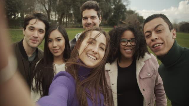 zeitlupenvideo einer multiethnischen gruppe von sechs freunden, die gemeinsam ein selfie machen - universitätsstudent stock-videos und b-roll-filmmaterial