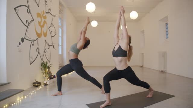 zeitlupenvideo einer privaten yogastunde eines personal trainers in einem yogastudio - yogastudio stock-videos und b-roll-filmmaterial
