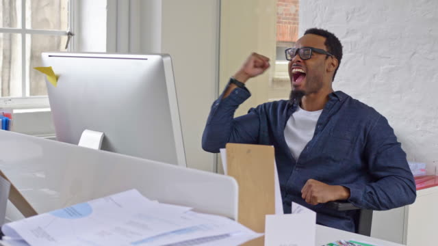 Slow motion video of a successful creative businessman celebrating good news at office