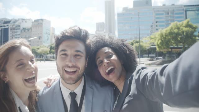 stockvideo's en b-roll-footage met slow motion video van een team van drie zakenmensen die samen een selfie in de stad nemen - avenida 9 de julio