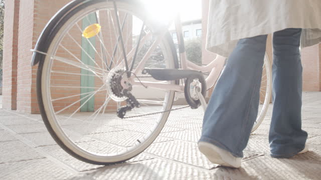 slow motion video of a woman walking while she's holding with her bike - close up shot of the legs and feet - jeans stock videos & royalty-free footage