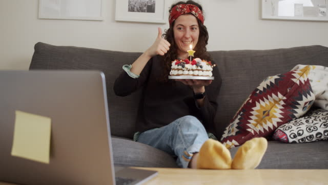 "slow motion video of a woman while she's celebrating her birthday ""virtually"" with friends and relatives, during a voip call - birthday cake stock videos & royalty-free footage"