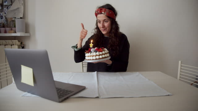 """slow motion video of a woman while she's celebrating her birthday """"virtually"""" with friends and relatives, during a voip call - birthday stock videos & royalty-free footage"""