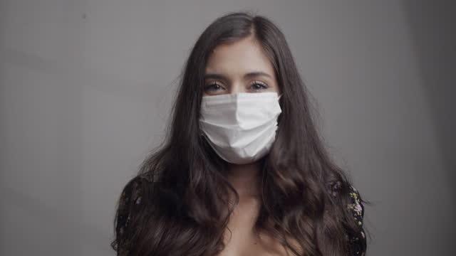 zeitlupe video von einem jungen erwachsenen schöne frau blick auf die kamera trägt eine schützende gesichtsmaske - caucasian ethnicity stock-videos und b-roll-filmmaterial