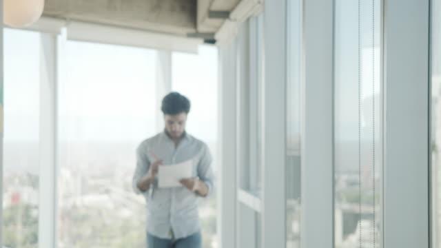 vídeos de stock e filmes b-roll de slow motion video of a young adult businessman in a modern office - nota mensagem