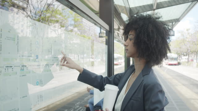 slow motion video of a young adult businesswoman looking at the map of a bus station in buenos aires - avenida 9 de julio stock videos & royalty-free footage