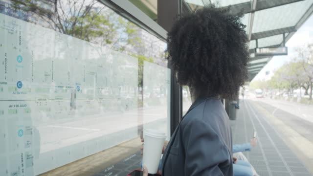 stockvideo's en b-roll-footage met slow motion video van een jonge volwassen onderneemster die de kaart van een buspost in buenos aires bekijkt - avenida 9 de julio
