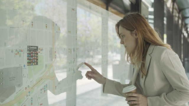 vídeos de stock e filmes b-roll de slow motion video of a young adult businesswoman looking at the map of a bus station in buenos aires - avenida 9 de julio