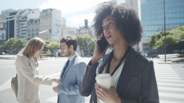 slow motion video of a young adult businesswoman using phone while she's waiting to cross te street in the city - avenida 9 de julio video stock e b–roll