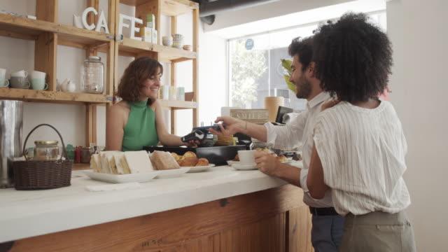 zeitlupenvideo eines jungen erwachsenen mannes, der im café mit dem handy bezahlt - bäckerei stock-videos und b-roll-filmmaterial