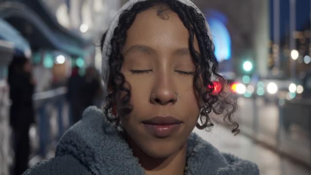 vídeos de stock, filmes e b-roll de vídeo em câmera lenta de uma jovem adulta olhando para a câmera à noite - tower bridge, londres. - olhos fechados