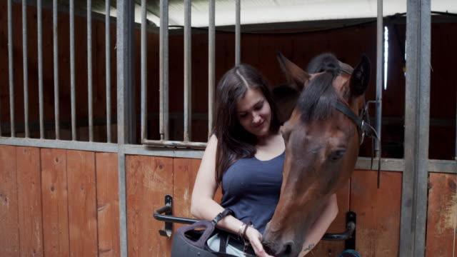 乗馬学校で彼女の馬の隣の若い大人の女性のスローモーションビデオ - 厩舎点の映像素材/bロール