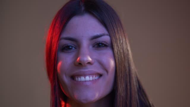 stockvideo's en b-roll-footage met slow motion video van een jonge volwassen vrouw die ogen opent en voor de camera met kleurrijke lichten glimlacht - waist up