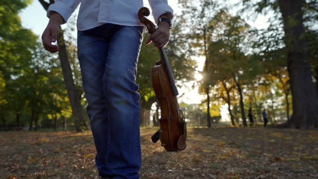 slow motion video of a young violinist enjoying a  walk in the park - musician stock videos & royalty-free footage