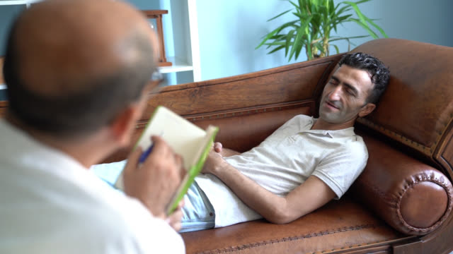 Slow Motion Video Of Adult Man Lying On Psychiatrist Couch While having Therapy