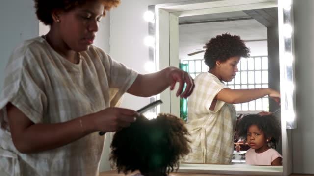 vídeos y material grabado en eventos de stock de video a cámara lenta de la madre afrocaribeña peinando el pelo de la hija de 3 años - peinado