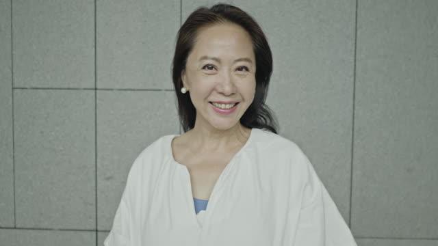 魅力的なアジアのシニア女性の笑顔のスローモーションビデオ - 中国人点の映像素材/bロール