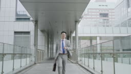 Slow motion video of Asian young businessman running to work