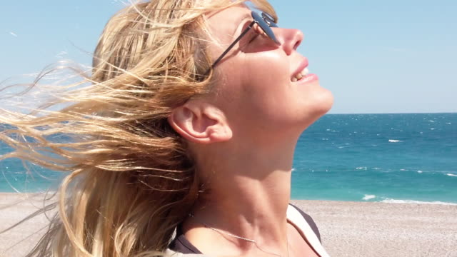 vídeos de stock e filmes b-roll de slow motion video of beautiful woman at the beach in a windy day - luz solar
