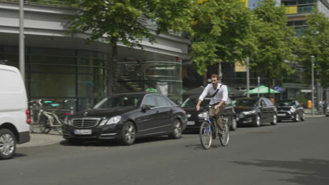 vídeos de stock e filmes b-roll de slow motion video of businessman commuting by bicycle in the streets of berlin - homens de idade mediana