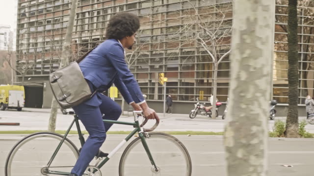 slow motion video of businessman commuting with his bicycle in the city - vita cittadina video stock e b–roll