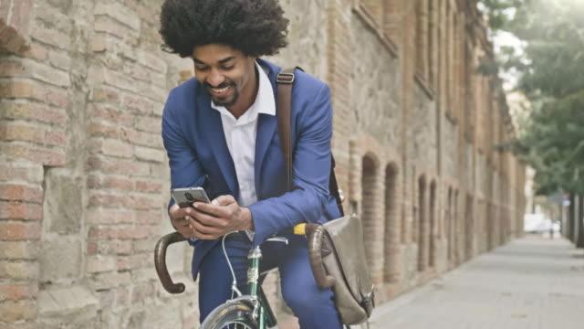 vídeos de stock, filmes e b-roll de vídeo de câmera lenta do empresário apoiando-se na sua bicicleta enquanto texting uma mensagem com seu telefone celular - millennial generation