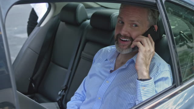Slow motion video of businessman on a taxi having a conversation on mobile phone