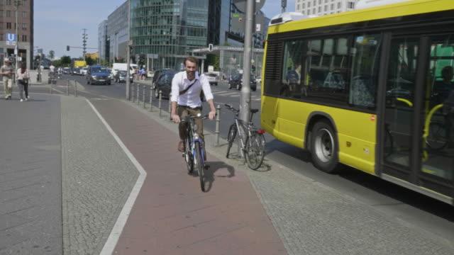 slow motion video der geschäftsmann mit dem fahrrad in der stadt - bus stock-videos und b-roll-filmmaterial