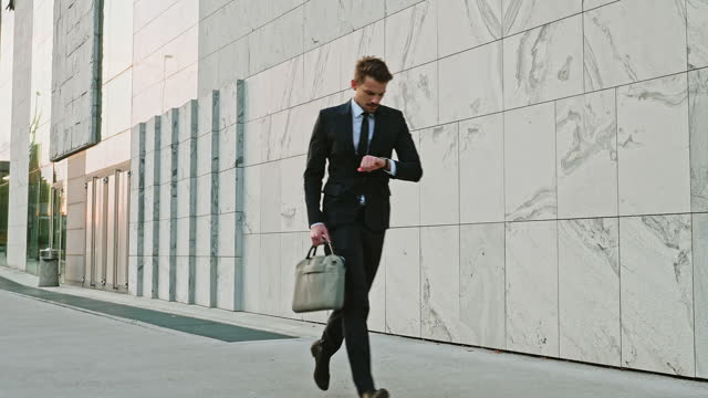 slow motion video of businessman running late to work - wrist watch stock videos & royalty-free footage