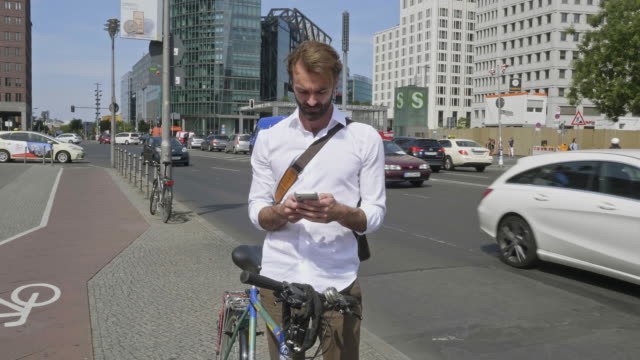 Slow motion video of businessman with his bicycle checking mobile at street