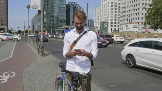 Slow Motion Video der Geschäftsmann mit seinem Fahrrad Check mobile Street